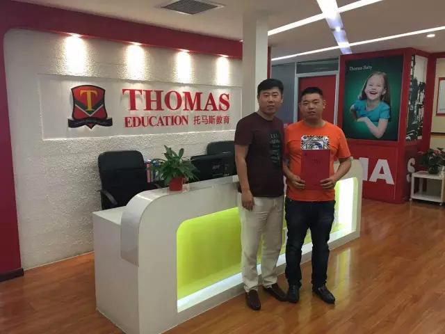 托马斯招商总监秦老师(左)与张先生(右)在总部签约后合影